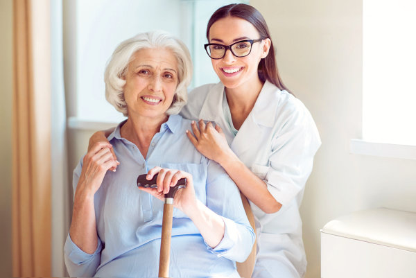 caregiver wearing a black glasses with an elderly woman